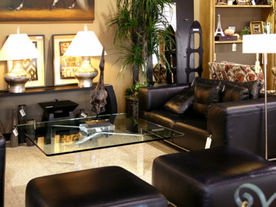 Black Leather Loveseat and 2 Ottomans Around a Glass Coffee Table
