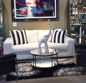 White Loveseat with Striped Pillows and Elephant Decoration